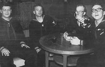 four sailors sitting at cocktail table